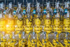 Hydraulic choke or throttle valves at offshore oil and gas wellhead remote platform. Hydraulic choke or throttle valves ninety degree angle valve type at oil and Royalty Free Stock Photography