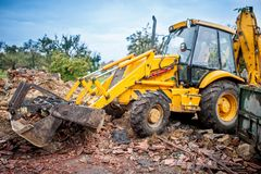 Hydraulic crusher, industrial excavator machinery working on site Stock Image