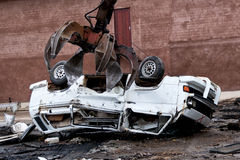 Hydraulic crushing machine crushing a vehicle. A crane crushing machine destroying a motor vehicle for scrap metal Stock Photo