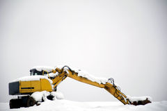 Hydraulic excavator covered with snow and not operating Stock Photo