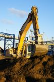 Hydraulic excavator at work. Shovel bucket against blue sky Stock Photo