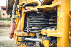 Hydraulic flexible pressure pipes and tubes. Close-up of industrial bulldozer with oil leaks Royalty Free Stock Images