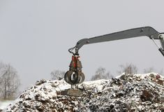 The hydraulic grab cleans and tampens the metal debris. The excavator lifts and throws the load with a pneumatic paw with claws. Hydraulic grab cleans and stock images