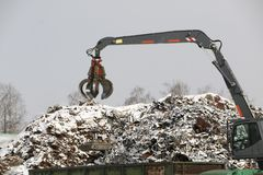 The hydraulic grab cleans and tampens the metal debris. The excavator lifts and throws the load with a pneumatic paw with claws. Hydraulic grab cleans and royalty free stock photography