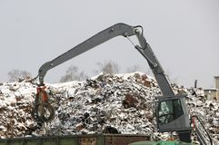 The hydraulic grab cleans and tampens the metal debris. The excavator lifts and throws the load with a pneumatic paw with claws. Hydraulic grab cleans and stock image