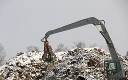 The hydraulic grab cleans and tampens the metal debris. The excavator lifts and throws the load with a pneumatic paw with claws. Hydraulic grab cleans and stock photography
