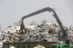 The hydraulic grab cleans and tampens the metal debris. The excavator lifts and throws the load with a pneumatic paw with claws. Hydraulic grab cleans and royalty free stock image