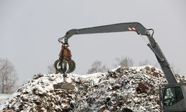 The hydraulic grab cleans and tampens the metal debris. The excavator lifts and throws the load with a pneumatic paw with claws. Hydraulic grab cleans and royalty free stock photos