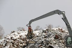The hydraulic grab cleans and tampens the metal debris. The excavator lifts and throws the load with a pneumatic paw with claws. Hydraulic grab cleans and royalty free stock photo