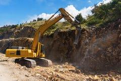 Hydraulic hammer destroys rock in road construction. Excavator with hydraulic breaker destroys rock in road construction stock photography