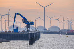 Hydraulic Harbor Crane. In the port of Eemshaven with oil tanks in background under setting sun stock image