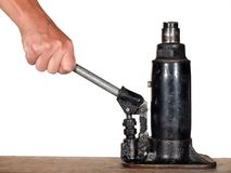 Hydraulic jack. Hand using automobile hydraulic bottle jack stock image