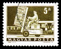 Hydraulic lift truck and mail car, Transport and Telecommunication serie, circa 1964. MOSCOW, RUSSIA - FEBRUARY 9, 2019: A stamp printed in Hungary shows royalty free stock image
