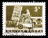 Hydraulic lift truck and mail car, Transport and Telecommunication serie, circa 1964. MOSCOW, RUSSIA - FEBRUARY 9, 2019: A stamp printed in Hungary shows royalty free stock images