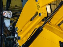 Lifting mechanism of loader. Hydraulic lifting cylinder and cab of the yellow forklift royalty free stock photo
