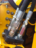 Hydraulic line and fittings. Some hydraulic lines and fittings on a large tractor or construction equipment Stock Image