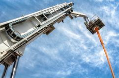 Hydraulic man lift. A hydraulic man lift extends up to blue sky stock image