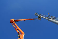 Hydraulic mobile construction platform elevated towards a blue sky with metal pole  street lamp Stock Photo