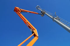Hydraulic mobile construction platform elevated towards a blue sky with metal pole street lamp Stock Photos