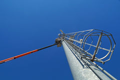 Hydraulic mobile construction platform elevated towards a blue sky with metal pole street lamp Stock Images