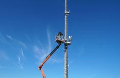 Hydraulic mobile construction platform elevated towards a blue sky with metal pole street lamp Royalty Free Stock Images