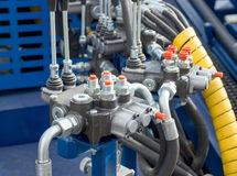 Hydraulic tubes, fittings and levers on control panel Royalty Free Stock Photos