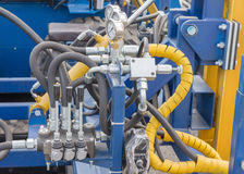 Hydraulic tubes, fittings and levers on control Stock Image