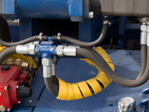 Hydraulic tubes, fittings and levers on control panel Stock Image