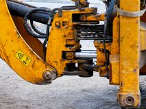 Hydraulical connections, piston on used yellow excavator. Close up shot at road construction site stock photography