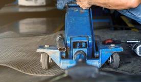 Hydrauliczne Podłogowe dźwigarki z mechanika mężczyzną dla samochodowej zawieszenie usługi w auto garażu i kopii przestrzeni zdjęcia stock