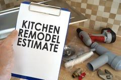 Hydraulik bierze schowek z kuchnią przemodelowywa kosztorys obraz stock