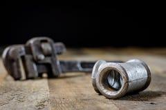 Hydraulik hjälpmedel för rörmokare på trätabellen Seminariet bordlägger a royaltyfri fotografi