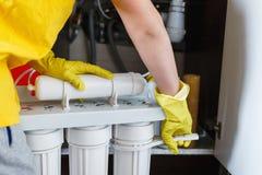 Hydraulik w żółtych gospodarstwo domowe rękawiczkach zmienia wodnych filtry Repairman zmienia wodne filtrowe ładownicy w kuchni p obraz stock