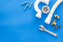 Hydraulika zawód z przekładnią i instrumentami dla remontowych tubk na błękitnym tło odgórnego widoku copyspace fotografia stock