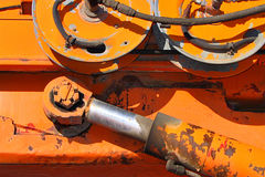 Hydrauling arm and wheels. Hose winding wheels and hydraulic arm on yellow or orange heavy industrial equipment Royalty Free Stock Photo