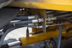 Hydraulisch systeemslangen en andere details van het gele close-up van wegmachines royalty-vrije stock afbeelding