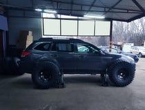 Hydraulische hefbomen voor een zwarte auto in de autoworkshop stock foto's