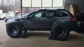 Hydraulische hefbomen voor een zwarte auto in de autoworkshop royalty-vrije stock foto's