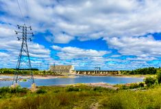 Landscape panoramic of hydro electric dam and power generating station.. Hydro electric dam and generating station; water churning and foaming down sluice in stock image