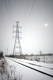 Hydro lines along train tracks in winter. Focus on a large hydro tower which runs along railroad tracks in winter, snow covering the ground, with the sun visible Stock Image