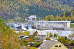 Hydro-power plant on the background of the autumn forest, mountains and village. Russia stock photography