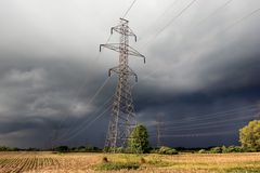 Hydro towers. In a farm field with impending thunderstorm in background Stock Photo