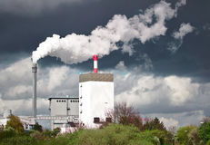 Hydroelectric power plant emitting white steam in front of a dark rain cloud Stock Photography
