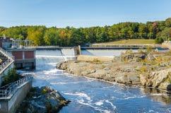 Hydroelektriskt Plat längs en flod och en blå himmel royaltyfri bild