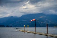 Hydroplane wiążący wodny aerodrom wiatrowy dmuchanie w windsock nad niebem i fotografia royalty free