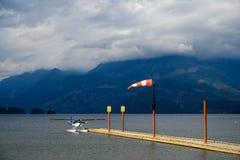 Hydroplane wiążący wodny aerodrom wiatrowy dmuchanie w windsock nad niebem i fotografia stock