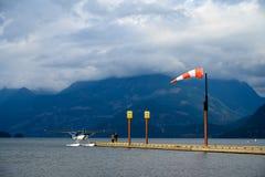 Hydroplane wiążący wodny aerodrom wiatrowy dmuchanie w windsock nad niebem i obraz royalty free