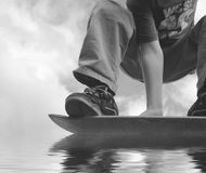 Hydroplaning skateboarder. Extreme skateboarder hydroplaning on water Royalty Free Stock Images