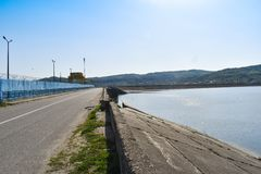 Hydropower dam on Olt river in a sunny spring day. Hydroelectric plant on the artificial lake stock photography