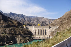 Hydropower plant in Kyrgyzstan on the Naryn River. View of the hydroelectric power plant in Kyrgyzstan on the Naryn river, hot summer, turquoise river. trip to Royalty Free Stock Photos